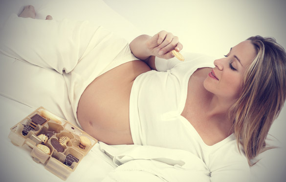 pregnant-woman-eating-cookies-in-bed
